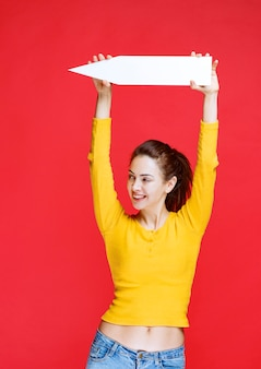 Chica sosteniendo una flecha apuntando hacia la izquierda