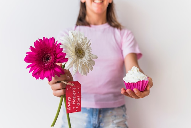 Chica sosteniendo flores con inscripción de feliz día de las madres