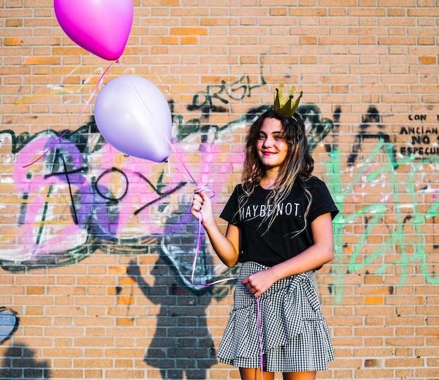 Chica sosteniendo globos delante de muro de grafiti