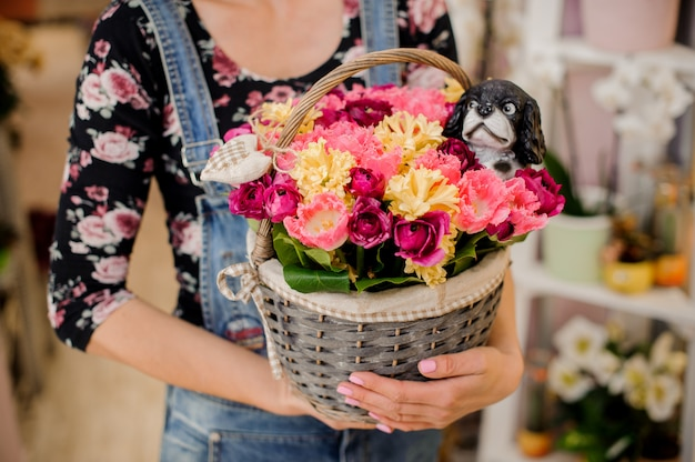 Chica sosteniendo una hermosa canasta de mimbre con flores.