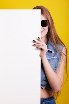 Chica sosteniendo una hoja en blanco, espacio para tu anuncio.