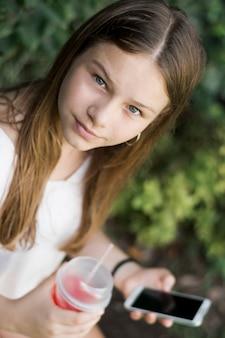 Chica sosteniendo jugo y celular mirando a cámara