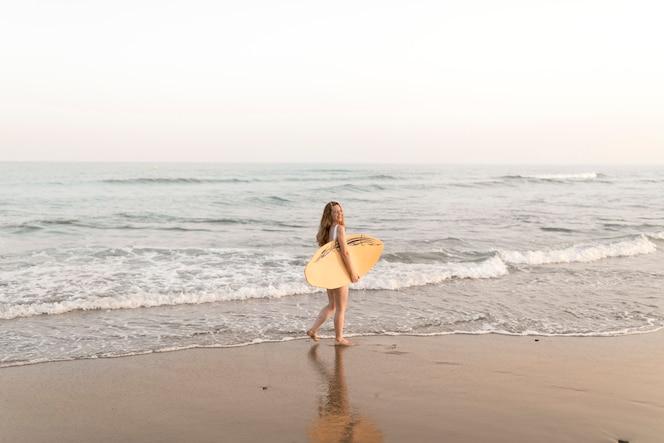 Chica sosteniendo la tabla de surf de pie cerca de la orilla del mar