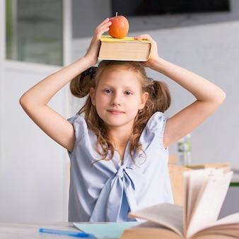 Chica sosteniendo un libro y una manzana en la cabeza