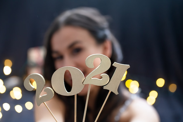 Chica sosteniendo en la mano el número del próximo año sobre un fondo borroso oscuro.