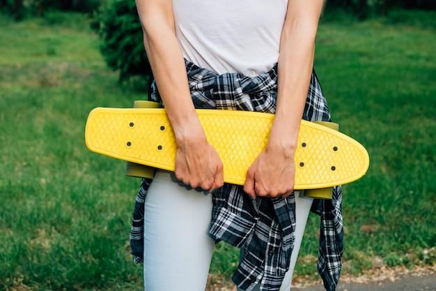 Chica sosteniendo un monopatín de plástico amarillo en el parque