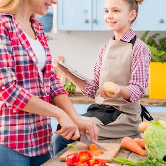 Chica sosteniendo papa y tableta digital en la mano mirando a su madre cortando verduras con un cuchillo