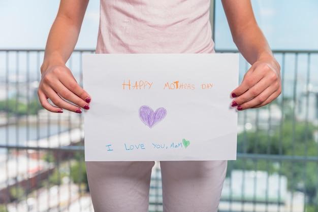Chica sosteniendo papel con inscripción feliz dia de la madre