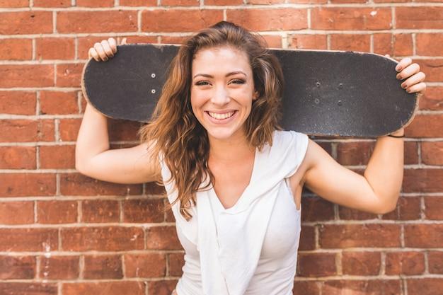 Chica sosteniendo una patineta y sonriendo, retrato contra una pared