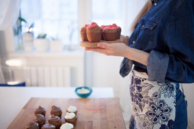 Chica sosteniendo un plato de magdalenas calientes frescas, borrosas