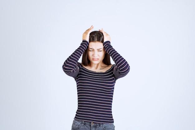 Chica sosteniendo su cabeza porque está cansada o tiene dolor de cabeza.