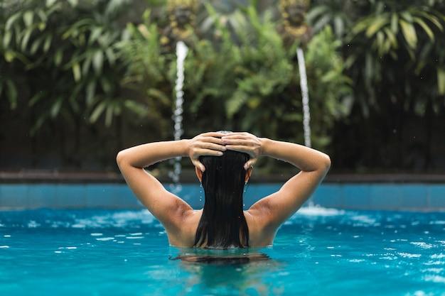 Chica está sosteniendo sus manos sobre su cabeza posando en la piscina.