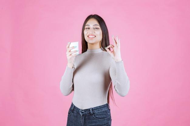 Chica sosteniendo una taza de café y apuntando al buen gusto