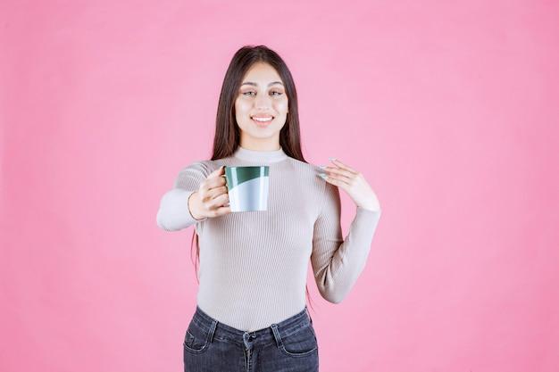 Chica sosteniendo una taza de café de color verde blanco y sintiéndose positivo