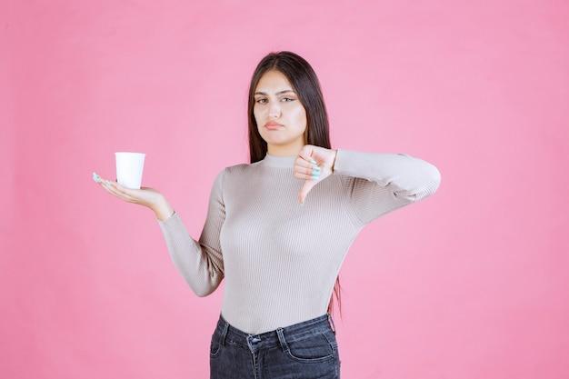Chica sosteniendo una taza de café y mostrando el pulgar hacia abajo signo