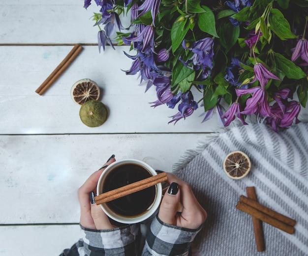 Chica sosteniendo una taza de té con canela y margarita ramo de pie a un lado