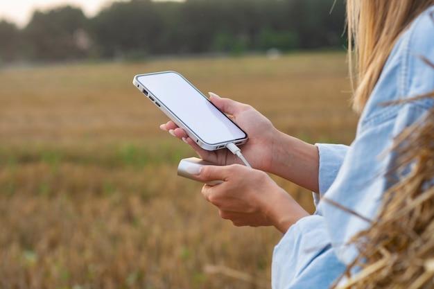 Chica sostiene una maqueta de un teléfono inteligente con una pantalla blanca en sus manos. power bank carga el teléfono en el contexto de la naturaleza.