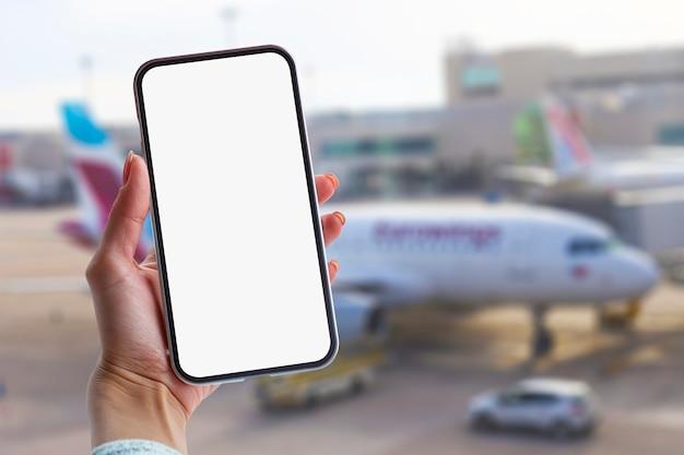 Chica sostiene una maqueta de un teléfono inteligente con un primer plano de pantalla en blanco. teléfono en el fondo del aeropuerto con un avión.