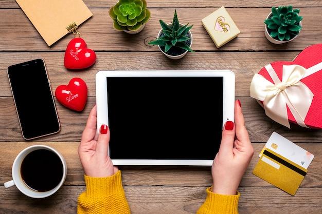 Chica sostiene tableta, tarjeta de débito, elige regalos, compra, taza de café, dos corazones