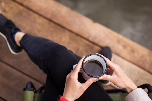 Chica sostiene una taza de café de metal en sus manos cerca del lago mientras está sentada en un muelle de madera.