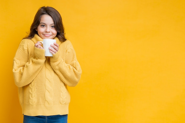 Chica de suéter amarillo con copa en las manos
