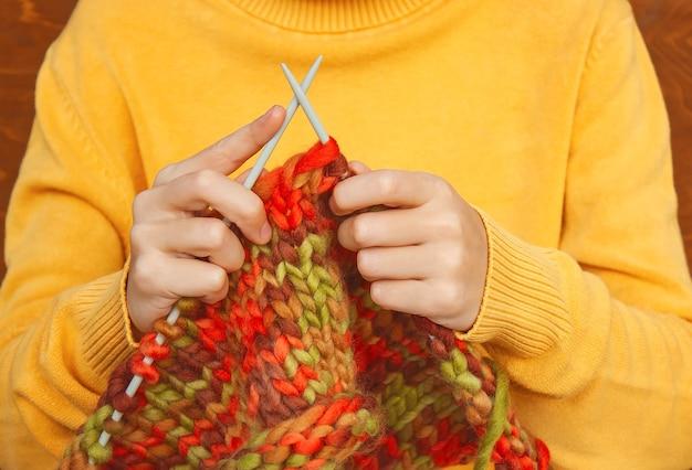 Chica en un suéter amarillo teje