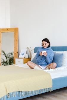 Chica en un suéter azul en el interior de estilo hygge con una taza de té caliente en sus manos se sienta en la cama