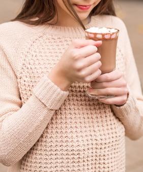 Chica con un suéter beige posando con un vaso de chocolate caliente en sus manos. foto
