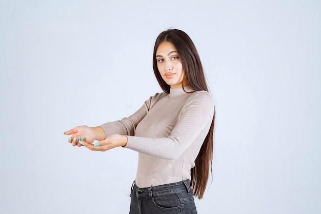 Chica en suéter gris abriendo sus manos.