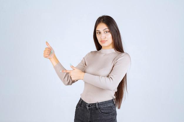 Chica en suéter gris haciendo pulgar arriba signo.