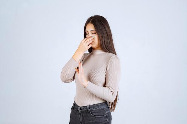 Chica en suéter gris siente mal olor y tapa la nariz.