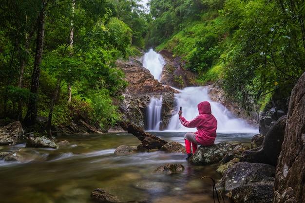 La chica de suéter rojo recorriendo la cascada pi-tu-gro, hermosa cascada en la provincia de tak, thailand.