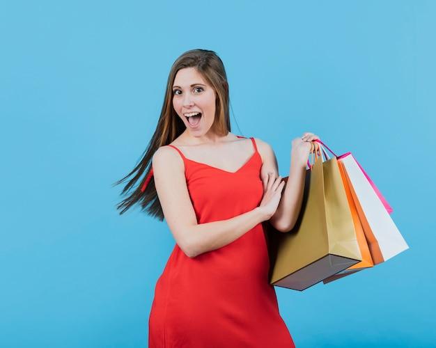 Chica sujetando bolsas de compras sobre fondo liso