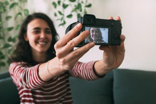 Chica sujetando la cámara para grabarse a sí misma en casa. enfoque selectivo en la cámara