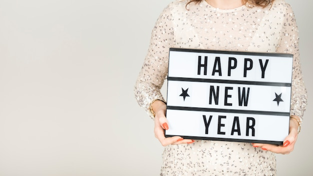 Chica sujetando cartel de feliz año nuevo