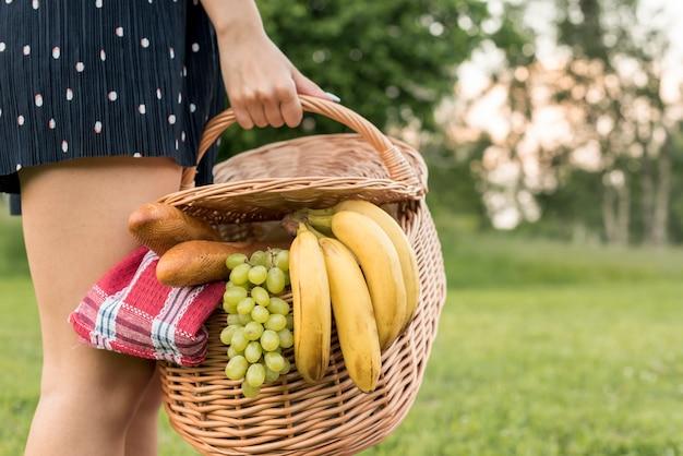 Chica sujetando cesta de picnic