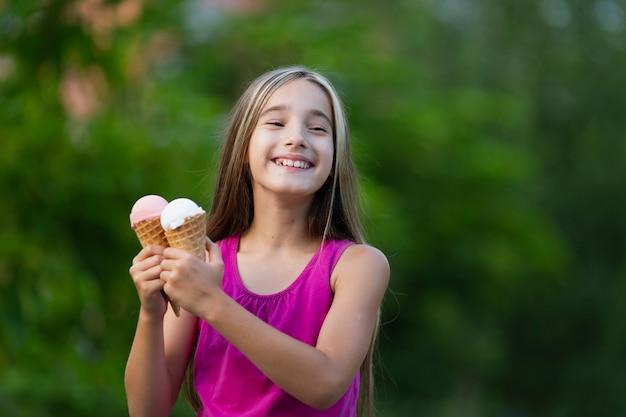 Chica sujetando conos de helado en el parque
