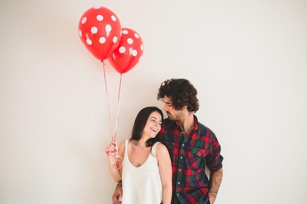 Chica sujetando dos globos con su novio al lado