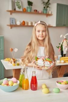 Chica sujetando galletas de pascua en la cocina