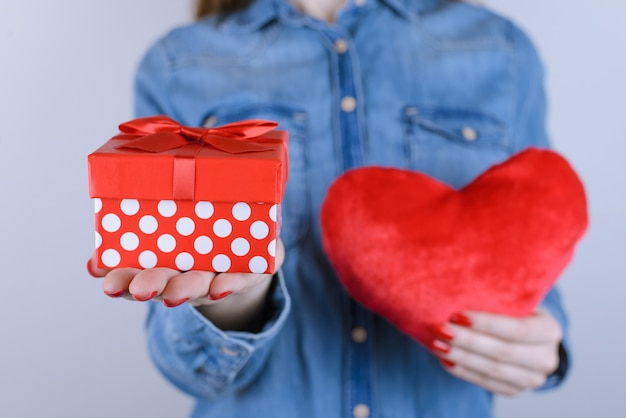Chica sujetando giftbox y corazón aislado fondo gris