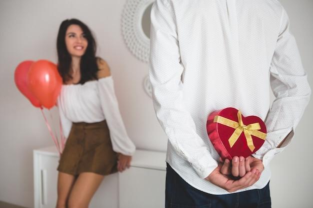 Chica sujetando globos con forma de corazón mientras su novio tiene un regalo para ella a la espalda