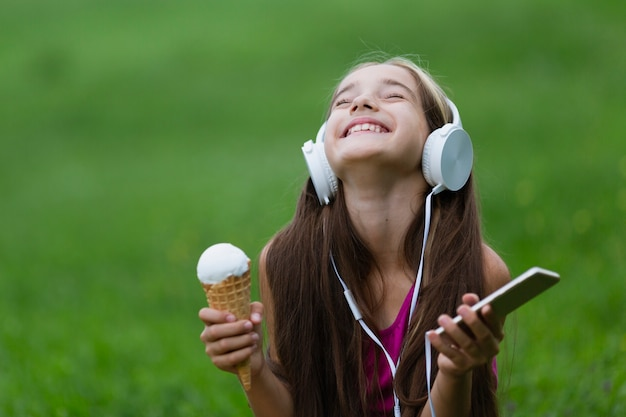 Chica sujetando helado de vainilla y teléfono