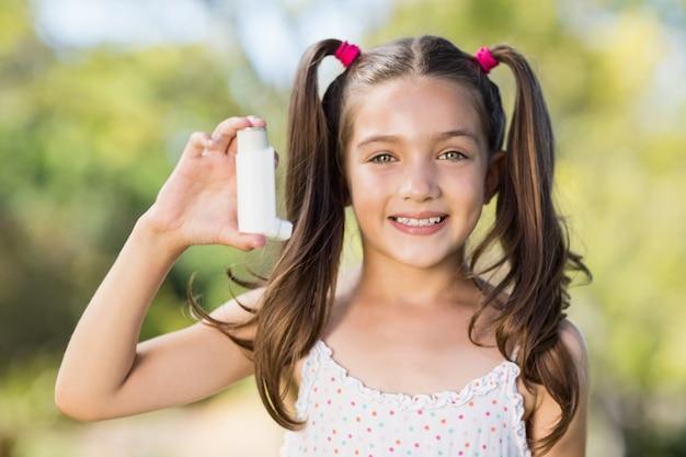 Chica sujetando un inhalador para el asma en el parque