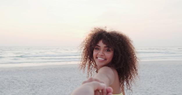 Chica sujetando la mano masculina y corriendo en la playa exótica tropical al océano
