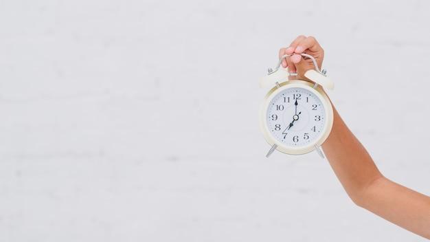 Chica sujetando un reloj con espacio de copia