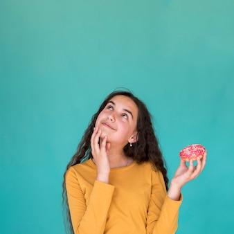 Chica sujetando una rosquilla glaseada con espacio de copia