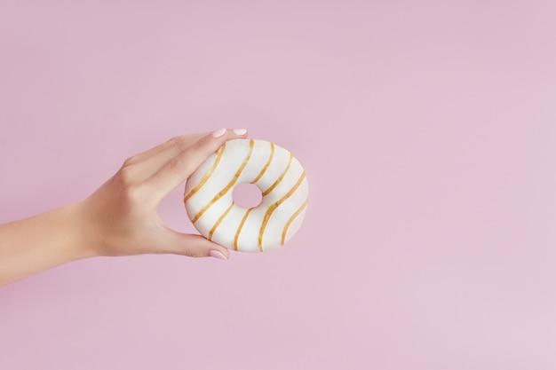 Chica sujetando una rosquilla en la mano sobre un fondo rosa