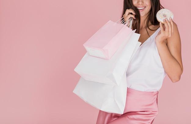 Chica sujetando una rosquilla y redes de compra