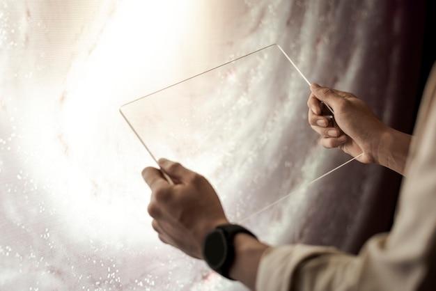Chica sujetando la tableta transparente en sus manos