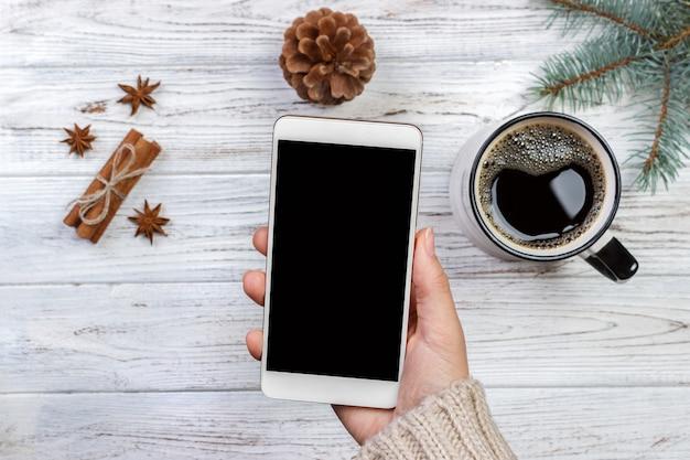 Chica sujetando el teléfono inteligente blanco en la mano en el escritorio de madera blanca rodeada de café y decoración navideña